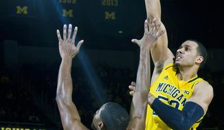 Michigan forward Jordan Morgan, right, takes a shot over Iowa forward Melsahn Basabe (1) in the first half of an NCAA college basketball game in Ann Arbor, Mich., Wednesday, Jan. 22, 2014. (AP Photo/Tony Ding)