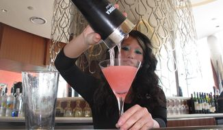In this April 8, 2013 photo, Mary Ma, a bartender at Revel Casino Hotel, pours a peach-flavored drink at the hotel, in Atlantic City, N.J. Atlantic City is increasing efforts to promote its nightlife, with luxury bus tours bringing Philadelphia partiers to Atlantic City, promotions aimed at bachelor and bachelorette parties, and summer-themed activities during the slow winter period. (AP Photo/Wayne Parry)