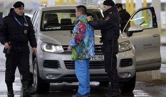 A Russian police officer searches a driver as his vehicle is also screened at an entrance to the Sochi 2014 Olympic Winter Games park, Thursday, Jan. 23, 2014, in Sochi, Russia. The Olympics begin on Feb. 7. (AP Photo/David J. Phillip)