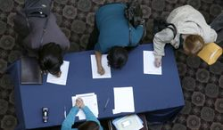 ** FILE ** In this Wednesday, Jan. 22, 2014, file photo, job seekers sign in before meeting prospective employers during a career fair at a hotel in Dallas. (AP Photo/LM Otero)