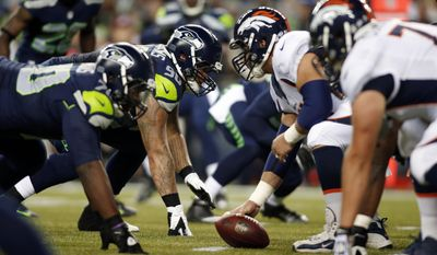 ADVANCE FOR WEEKEND EDITIONS, JAN. 25-26 - FILE - In this Aug. 17, 2013, file photo, Seattle Seahawks' Jesse Williams (90) lines up with teammates at the line of scrimmage against the Denver Broncos in the second half of a preseason NFL football game,  in Seattle. The two teams are slated to meet in Super Bowl XLVIII on Sunday, Feb. 2, 2014, in East Rutherford, N.J. (AP Photo/John Froschauer, File)
