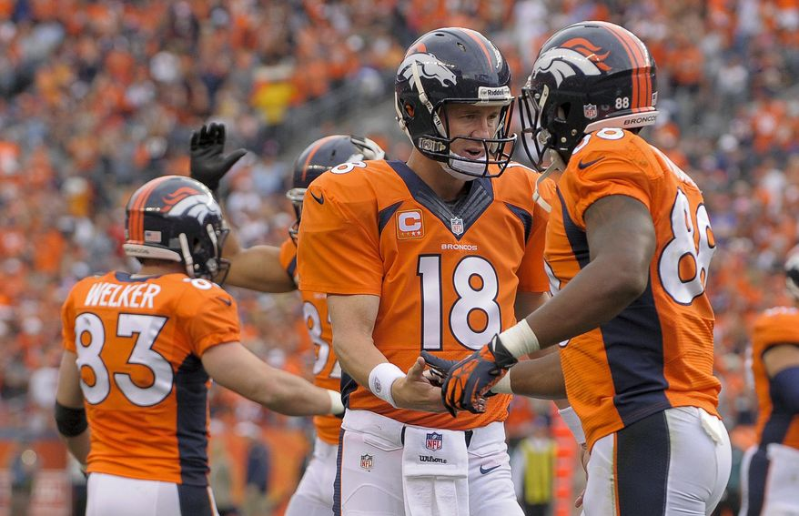 ADVANCE FOR WEEKEND EDITIONS, JAN. 25-26 - In this Sept. 29, 2013, file photo, Denver Broncos quarterback Peyton Manning (18) is congratulated by wide receiver Demaryius Thomas (88) after throwing a touchdown pass to Wes Welker during the third quarter of an NFL football game against the Philadelphia Eagles in Denver.  No team in the 93-year history of the NFL ever had that many players catch at least 60 passes or reach the end zone 10 or more times until the Broncos put up a record 606 points. (AP Photo/Jack Dempsey, File)