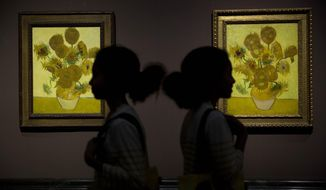 """Identical twins Ella, left, and Eva, aged 12, pose for photographers in front of two versions of Dutch-born painter Vincent van Gogh's """"Sunflowers"""", the left one from 1888 and the right one from 1889, during a photocall at the National Portrait Gallery in London, Friday, Jan. 24, 2014.  The two paintings are being reunited in London for the first time in 65 years, with the 1889 version on loan from the Van Gogh Museum in Amsterdam.  They will be displayed together until April 27.  (AP Photo/Matt Dunham)"""