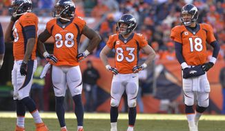 ADVANCE FOR WEEKEND EDITIONS, JAN. 25-26 - In this Jan. 12, 2014, file photo, Denver Broncos tight end Julius Thomas (80), wide receiver Demaryius Thomas (88), wide receiver Wes Welker (83) and quarterback Peyton Manning (18) wait as officials review a fumbled pass by Thomas during the second quarter against the San Diego Chargers in an AFC divisional NFL playoff football game in Denver.  No team in the 93-year history of the NFL ever had that many players catch at least 60 passes or reach the end zone 10 or more times until the Broncos put up a record 606 points. (AP Photo/Jack Dempsey, File)