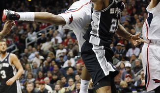 San Antonio Spurs power forward Tim Duncan (21) passes as Atlanta Hawks point guard Jeff Teague (0) defends in the first half of an NBA  basketball game, Friday, Jan. 24, 2014, in Atlanta.  Teague was injured on the play and left the game. (AP Photo/John Bazemore)