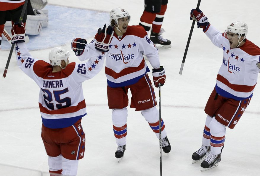 Washington Capitals left wing Jason Chimera (25) celebrates with teammates Jay Beagle, center, and Tom Wilson after Chimera scored a goal against the New Jersey Devils during the third period of an NHL hockey game, Friday, Jan. 24, 2014, in Newark, N.J. The Devils won 2-1. (AP Photo/Julio Cortez)
