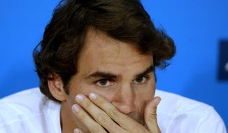 Roger Federer of Switzerland speaks during a press conference after his semifinal loss to Rafael Nadal of Spain at the Australian Open tennis championship in Melbourne, Australia, Friday, Jan. 24, 2014. (AP Photo/Aijaz Rahi)