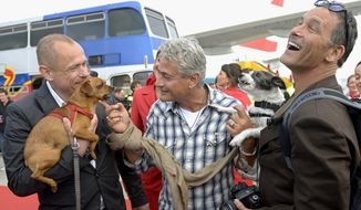 FILE - In this May 24, 2014 file photo, Gery Keszler, left, organizer and founder of the Life Ball, former U.S. Olympian diver Greg Louganis, center, and Daniel McSwiney pose at the Vienna International Airport in Austria. Louganis will be part of the broadcast crew covering the Westminster dog show events in February 2014, and will work for Fox Sports 1 at the agility competition on Feb. 8. (AP Photo/Hans Punz, File)
