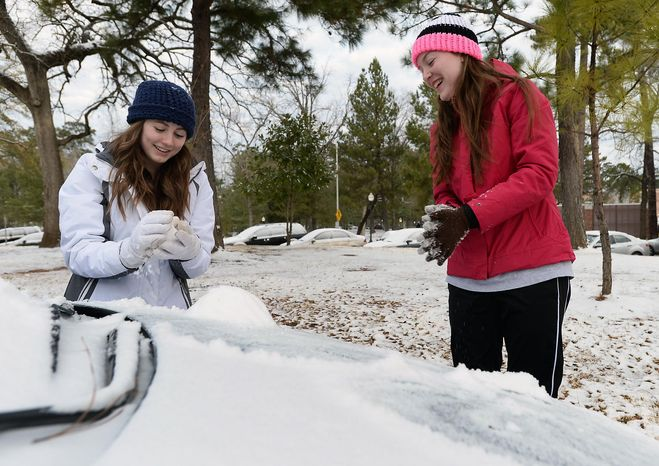 Stephen F. Austin State freshmen Tara Ramsey, left, of Mont Belvieu, Texas, and Makenzie Dickins of Livingston, Texas, build a miniature snowman on the hood of a car Friday, Jan. 24, 2014 on the SFA campus in Nacogdoches, Texas. The girls were enjoying an unexpected day off after campus offices were closed and classes were cancelled due to a winter storm that moved through th