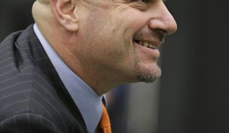 Cleveland Browns coach Mike Pettine smiles as owner Jimmy Haslam speaks to the media Thursday, Jan. 23, 2014, in Berea, Ohio. Buffalo's defensive coordinator, who met with team officials for the first time just a week ago, finalized a contract Thursday to become the NFL football team's seventh full-time coach since 1999. (AP Photo/Tony Dejak)