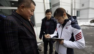 Kim Yuna, Vancouver gold medalist for the women's figure skating, signs her autograph for a fan prior to the inaugural ceremony of South Korean national team for the Sochi Winter Olympics in Seoul, South Korea, Thursday, Jan. 23, 2014. South Korea will send 64 athletes to Sochi which will be held from Feb. 7-23. (AP Photo/Lee Jin-man)