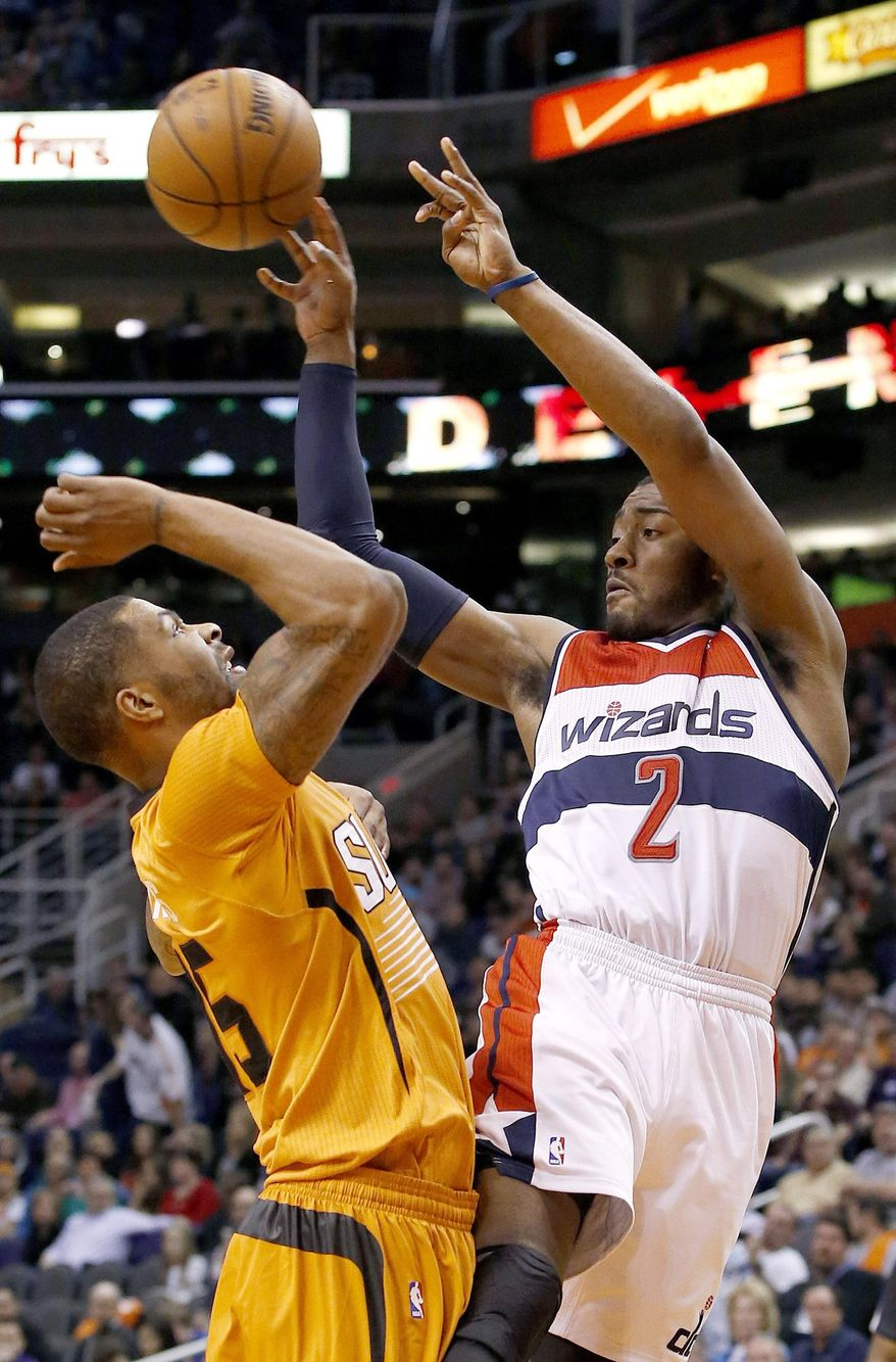 Washington Wizards' John Wall (2) passes the ball off as Phoenix Suns' Marcus Morris, left, defends during the first half of an NBA basketball game, Friday, Jan. 24, 2014, in Phoenix. (AP Photo/Ross D. Franklin)
