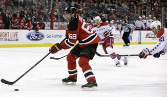 New Jersey Devils right wing Jaromir Jagr (68), of the Czech Republic, skates with the puck as Washington Capitals center Brooks Laich (21) and left wing Jason Chimera, back, chase after him during the second period of an NHL hockey game, Friday, Jan. 24, 2014, in Newark, N.J. Jagr had two assists in the Devils' 2-1 victory. (AP Photo/Julio Cortez)