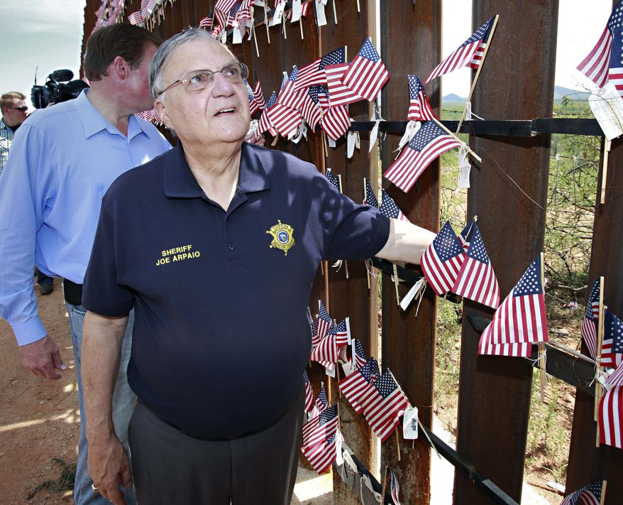 **FILE** Maricopa County Sheriff Joe Arpaio looks at the flags hanging on the International border wall Sunday, Aug. 15, 2010 in Hereford, Ariz. at a United Border Coalition Tea Party Rally.  (AP Photo/Matt York)