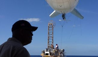**FILE** U.S. Navy Rear Admiral Sinclair Harris looks at a balloon-like craft known as an aerostat that is attached to the back of his high speed vessel Swift docked in Key West, Fla., on April 26, 2013. The U.S. Navy began testing two new aerial tools, borrowed from the battlefields of Afghanistan and Iraq, that officials say will make it easier to detect, track and videotape drug smugglers in action. (Associated Press)