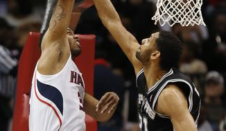 Atlanta Hawks power forward Mike Scott (32) has his shot blocked by San Antonio Spurs power forward Tim Duncan (21) in the first half of an NBA basketball game  Friday, Jan. 24, 2014, in Atlanta.  (AP Photo/John Bazemore)