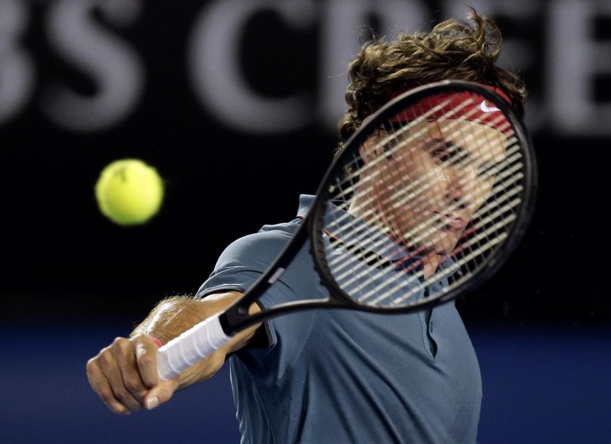 Roger Federer of Switzerland makes a backhand return to Rafael Nadal of Spain during their semifinal at the Australian Open tennis championship in Melbourne, Australia, Friday, Jan. 24, 2014.(AP Photo/Rick Rycroft)