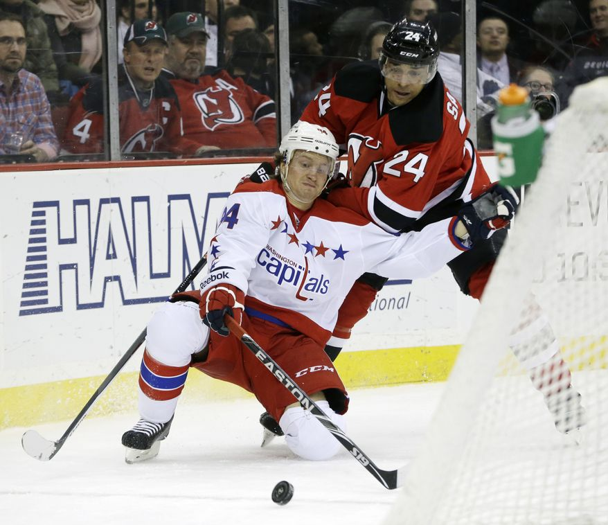Washington Capitals center Mikhail Grabovski, bottom, of Germany, is challenged by New Jersey Devils defenseman Bryce Salvador during the first period of an NHL hockey game, Friday, Jan. 24, 2014, in Newark, N.J. (AP Photo/Julio Cortez)