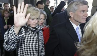 CORRECTS TO SAY THAT MAUREEN MCDONNELL IS AT CENTER INSTEAD OF LEFT - Former Virginia Gov. Bob McDonnell, right, and his wife, Maureen, center, behind McDonnell, are surrounded by family and supporters as they leave Federal court in Richmond, Va., Friday, Jan. 24, 2014.  McDonnell and his wife pleaded not guilty Friday to federal charges that they traded their influence for tens of thousands of dollars in gifts and loans, and both will be allowed to remain free until their trial. (AP Photo/Steve Helber)
