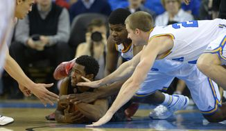 Stanford guard Chasson Randle, second from left, tries to hold on to a loose ball as teammate forward Dwight Powell, left, reaches in along with UCLA forward Tony Parker, second from left, and forward Travis Wear during the first half of an NCAA college basketball game, Thursday, Jan. 23, 2014, in Los Angeles. (AP Photo/Mark J. Terrill)