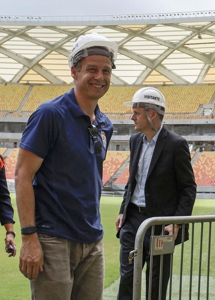 Head coach of United States soccer team, Jurgen Klinsmann, from Germany, left, visits the Arena da Amazonia stadium in Manaus, Brazil, Friday, Jan. 24, 2014. Manaus is one of the host cities for the 2014 World Cup, and will host a game between the U.S. and Portugal. (AP Photo/Raphael Alves)