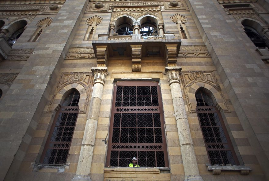 An Egyptian worker peers from the window of the damaged Museum of Islamic Art after an explosion at the Egyptian police headquarters in downtown Cairo, Friday, Jan. 24, 2014. Egypt's antiquities minister says the car bombing that struck the main police headquarters in Cairo earlier in the day has caused major damage to the nearby Islamic art museum.(AP Photo/Khalil Hamra)