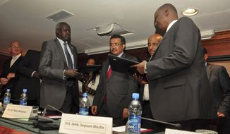 Nhail Deng Nhail, 2nd left, the head of South Sudan's negotiating team, and top negotiator for the rebel's side, Taban Deng Gai, right, a general in South Sudan's army before he defected, sign a cessation of hostilities agreement in front of mediator Ethiopian Foreign Minister Tedros Adhanom, center, in Addis Ababa, Ethiopia Thursday, Jan. 23, 2014. South Sudan's government and rebels fighting against it have signed Thursday a cessation of hostilities agreement in Addis Ababa that should at the least put a pause to five weeks of warfare that has claimed thousands of lives and uprooted a half million people since fighting began Dec. 15 between the government and supporters of former Vice President Riek Machar. (AP Photo/Elias Asmare)