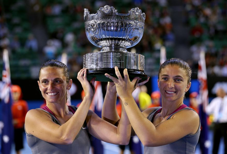Italy's Sara Errani, right, and Roberta Vinci hold the championship trophy after defeating Russia's Ekaterina Makarova and Elena Vesnina in their women's doubles final at the Australian Open tennis championship in Melbourne, Australia, Friday, Jan. 24, 2014.(AP Photo/Aaron Favila)