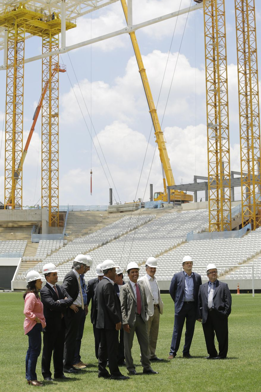Members of FIFA and the 2014 World Cup Local Organizing Committee inspect Arena de Sao Paulo stadium, in Sao Paulo, Brazil, Monday, Jan. 20, 2014. The commission started an inspection tour of stadiums in host cities across Brazil. (AP Photo/Nelson Antoine)