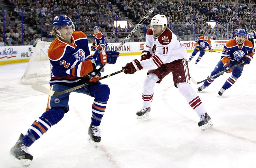Phoenix Coyotes' Martin Hanzal (11) slashes Edmonton Oilers' Jeff Petry (2) as Oilers' Boyd Gordon (27) chases the puck during the first period of an NHL hockey game Friday, Jan. 24, 2014, in Edmonton, Alberta. (AP Photo/The Canadian Press, Jason Franson)