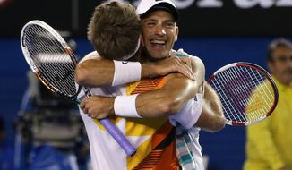 Lukasz Kubot of Poland, right, and Robert Lindstedt of Sweden celebrate after defeating Eric Butorac of the U.S. and Raven Klaasen of South Africa in their men's doubles final at the Australian Open tennis championship in Melbourne, Australia, Saturday, Jan. 25, 2014.(AP Photo/Aaron Favila)