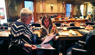 In this Jan. 22, 2014 photo, Colorado Democratic state senators Mary Hodge, left, and Gail Schwartz talk inside the chambers of the Colorado State Senate, at the Capitol, in Denver. Sen. Hodge has proposed a bill requiring better informing landowners and buyers about their property rights, which often doesn't include mineral rights below the surface. (AP Photo/Brennan Linsley)