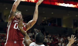 Oklahoma's Ryan Spangler shoots under pressure from Texas Tech's Toddrick Gotcher (20) during an NCAA college basketball game in Lubbock, Texas, Saturday, Jan. 25, 2014. (AP Photo/The Avalanche-Journal, Tori Eichberger)