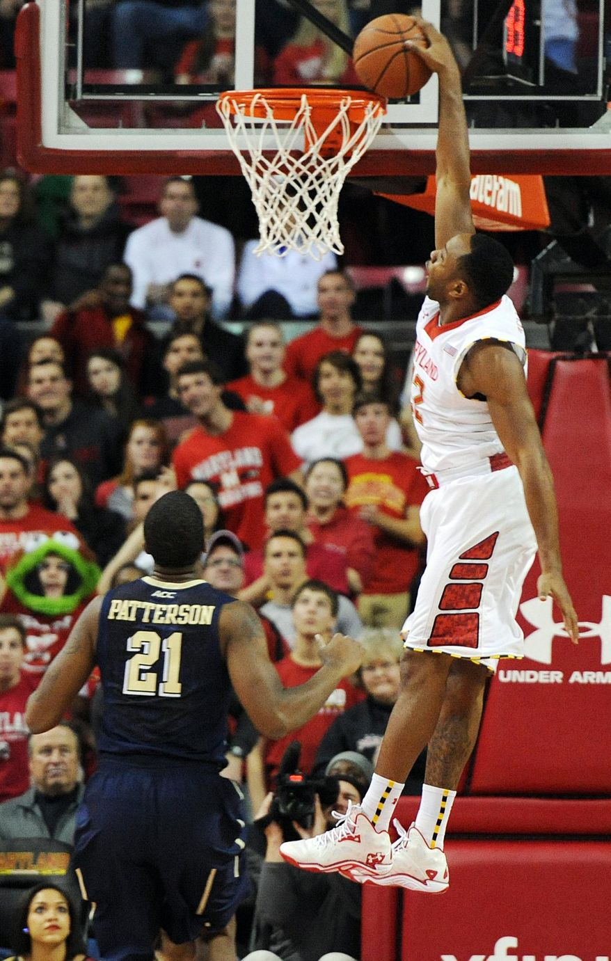 Maryland's Dez Wells, right, scores as Pittsburgh's Lamar Patterson stands near in the first half of an NCAA college basketball game Saturday, Jan. 25, 2014, in College Park, Md. (AP Photo/Gail Burton)