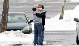 Two people embrace in the parking lot at the scene of a shooting at The Mall in Columbia on Saturday, Jan. 25, 2014 in Columbia, Md. Police say three people died in a shooting at the mall in suburban Baltimore, including the presumed gunman.(AP Photo/ Evan Vucci)