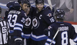 Winnipeg Jets' Dustin Byfuglien (33), Bryan Little, Andrew Ladd (16) and Jacob Trouba (8) celebrate Byfuglien's overtime goal that gave the Jets a 5-4 win over the Toronto Maple Leafs in an NHL hockey game Saturday, Jan. 25, 2014, in Winnipeg, Manitoba. (AP Photo/The Canadian Press, Jason Woods)