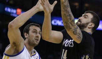 Minnesota Timberwolves' Nikola Pekovic, right, lays up a shot against Golden State Warriors' Andrew Bogut (12) during the first half of an NBA basketball game, Friday, Jan. 24, 2014, in Oakland, Calif. (AP Photo/Ben Margot)