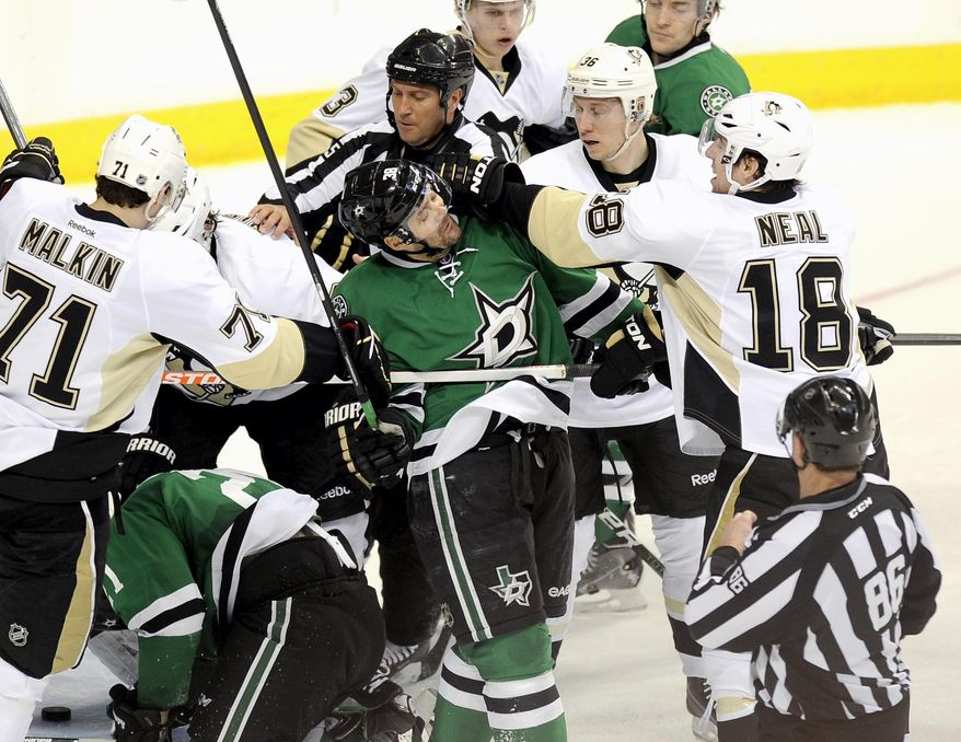 Players from both teams are separated as Pittsburgh Penguins left wing James Neal (18) and Dallas Stars center Vernon Fiddler (38) exchange punches in the first period during an NHL hockey game, Saturday, Jan. 25, 2014, in Dallas. (AP Photo/Matt Strasen)