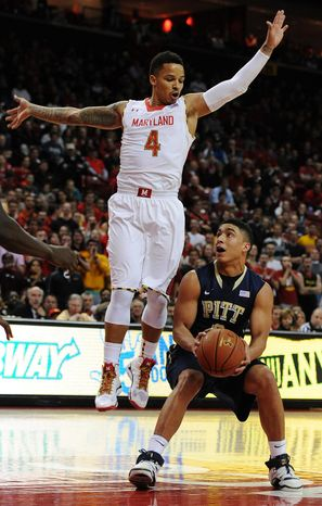 Maryland's Seth Allen, left, jumps to block as Pittsburgh's James Robinson looks to shoot in the first half of an NCAA college basketball game Saturday, Jan. 25, 2014, in College Park, Md. (AP Photo/Gail Burton)