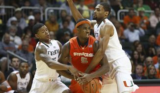 Miami players Rion Brown, left, and Donnavan Kirk, right, block Syracuse's C.J. Fair (5) during the second half of a NCAA college basketball game in Coral Gables, Fla., Saturday, Jan. 25, 2014. Syracuse won 64-52. (AP Photo/J Pat Carter)
