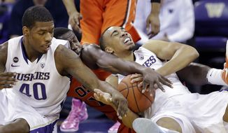 Oregon State's Daniel Gomis, center, is trapped between Washington's Shawn Kemp Jr. (40) and Andrew Andrews during the first half of an NCAA college basketball game Saturday, Jan. 25, 2014, in Seattle. (AP Photo/Elaine Thompson)