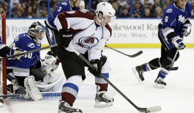 Colorado Avalanche center Matt Duchene (9) carries the puck around Tampa Bay Lightning goalie Ben Bishop (30), defenseman Keith Aulie (3) and defenseman Sami Salo (6), of Finland, during the first period of an NHL hockey game Saturday, Jan. 25, 2014, in Tampa, Fla. (AP Photo/Chris O'Meara)