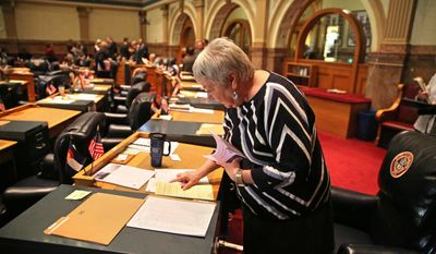 In this Jan. 22, 2014 photo, Colorado Democratic state senator Mary Hodge does some reading at her desk inside the chambers of the Colorado State Senate, at the Capitol, in Denver. Sen. Hodge has proposed a bill requiring better informing landowners and buyers about their property rights, which often doesn't include mineral rights below the surface. (AP Photo/Brennan Linsley)