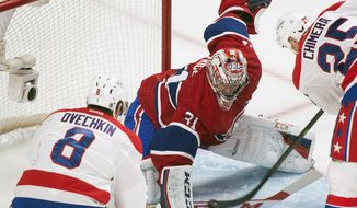 Washington Capitals' Alex Ovechkin, left, and teammate Jason Chimera, right, move in on Montreal Canadiens goaltender Carey Price during the second period of an NHL hockey game in Montreal, Saturday, Jan. 25, 2014. (AP Photo/The Canadian Press, Graham Hughes)