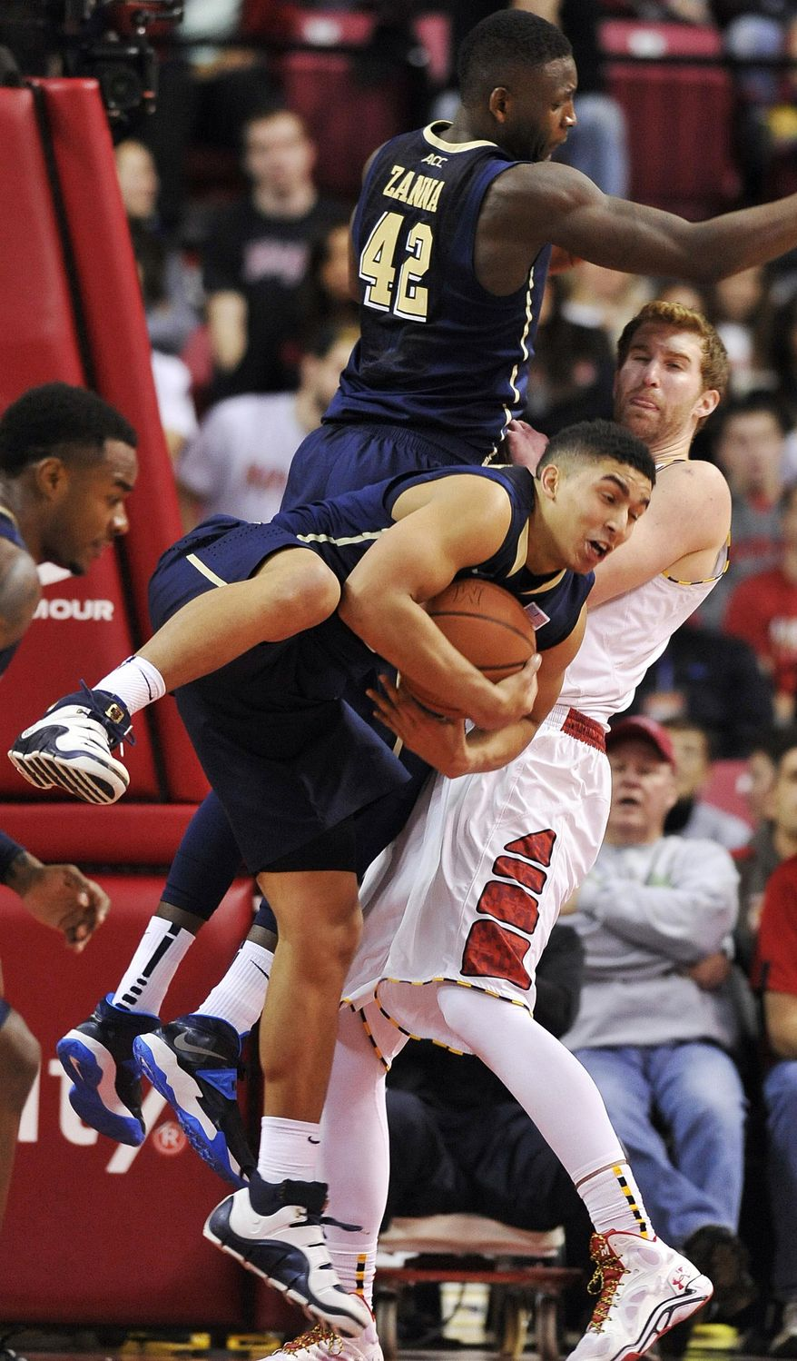 Pittsburgh's James Robinson, center front, comes down with a rebound in front of team mate Talib Zanna, behind, and Maryland's Evan Smotrycz, right, in the second half of an NCAA college basketball game Saturday, Jan. 25, 2014, in College Park, Md. Pittsburgh won 83-79. (AP Photo/Gail Burton)