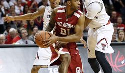 Texas Tech's Robert Turner, left, and Jaye Crockett, right, put pressure on Oklahoma's Cameron Clark during an NCAA college basketball game in Lubbock, Texas, Saturday, Jan. 25, 2014. (AP Photo/The Avalanche-Journal, Tori Eichberger)