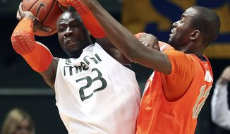 Syracuse' Baye Moussa Keita, right, pressures Miami's Russ DeRemer (23) during the first half of an NCAA college basketball game in Coral Gables, Fla., Saturday, Jan. 25, 2014. (AP Photo/J Pat Carter)