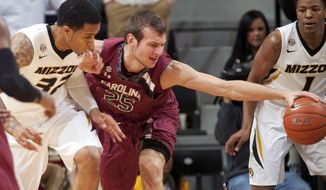 South Carolina's Mindaugas Kacinas, center, pulls in the ball between Missouri's Jabari Brown, left, and Wes Clark, right, during the first half of an NCAA college basketball game Saturday, Jan. 25, 2014, in Columbia, Mo. (AP Photo/L.G. Patterson)