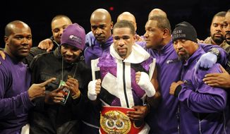 Lamont Peterson, center, poses with the belt after he beat Dierry Jean, of Canada, in the IBF Junior welterweight title boxing match, Saturday, Jan. 25, 2014, in Washington. (AP Photo/Nick Wass)