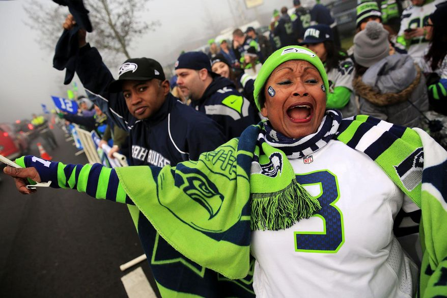 Marcia Shiri-Wasto, center, cheers with Seattle football fans on South 188th Street in SeaTac, Wash. Sunday, Jan. 26, 2014. The Seahawks drove past the crowd on route to the airport for Super Bowl XLVIII. (AP Photo/The Seattle Times, Erika Schultz) OUTS: SEATTLE OUT, USA TODAY OUT, MAGAZINES OUT, TELEVISION OUT, SALES OUT. MANDATORY CREDIT TO:  ERIKA SCHULTZ / THE SEATTLE TIMES